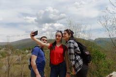Gruppen av vänner fotvandrar i berg Tre ungdomarsom går till och med bygd Arkivfoto