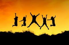 Gruppen av vänner hoppar på överkanten av berget arkivbilder