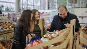 Gruppen av vänner i en supermarket väljer och sätter i den shoppa vagnen av julleksaker, ljust kulört dekorativt arkivfilmer