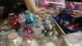 Gruppen av vänner i en supermarket väljer och sätter i den shoppa vagnen av julleksaker, ljust kulört dekorativt lager videofilmer