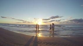 Gruppen av vänner som kör på sandigt, blöter stranden in mot havet och att reta sig i vattnet lager videofilmer
