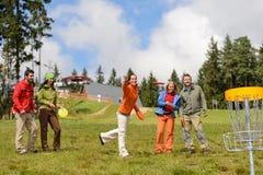 Grupp av vänner som leker med flygdisketten Royaltyfri Foto