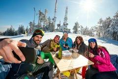 Gruppen av vänner som skrattar och tycker om i drink på, skidar semesterorten royaltyfria foton