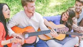 Gruppen av v?nner som spelar gitarrer och sjunger, medan dricka r?tt vin som sitter p? gr?s i, parkerar utomhus- arkivbilder
