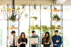 Gruppen av vänner som står på tabellen och alla, använder hans divices i modernt kontorsrum Tillsammans gyckel i apparat royaltyfri fotografi
