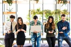 Gruppen av vänner som står på tabellen och alla, använder hans divices i modernt kontorsrum Tillsammans gyckel i apparat fotografering för bildbyråer