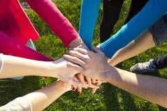Gruppen av vänner traver upp händer som enheted Royaltyfri Bild