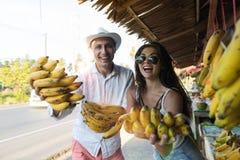 Gruppen för bananer för gladlynta barnpar bär frukt den hållande på lyckliga le turister för gatamarknad i asiat basaren Fotografering för Bildbyråer
