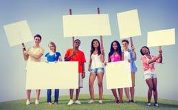 Gruppen-Freunde draußen bekleben den Ausdruck mit Plakaten, der Team Concept zujubelt Lizenzfreie Stockbilder