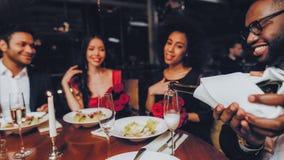 Gruppen-glückliche Freunde, welche die Datierung in Restaurant genießen stockfotografie