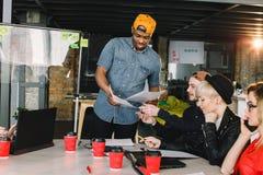Gruppen-junge Gesch?ftsleute erfasst kreative Idee zusammen, besprechend Gruppe internationale Studenten, die bei Tisch sitzen lizenzfreies stockfoto