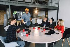 Gruppen-junge Gesch?ftsleute erfasst kreative Idee zusammen, besprechend Gruppe internationale Studenten, die bei Tisch sitzen stockbild