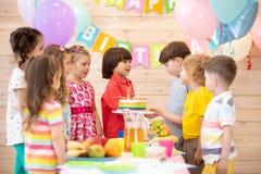 Gruppen Kinder kommen zu den Partei- und Erschütterungshänden mit einem Geburtstagsjungen Nette hübsche Kinder sind gekommen zu b stockfotografie
