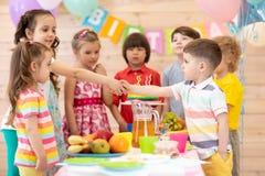 Gruppen Kinder kommen zu den Parteien und zu den Ersch?tterungsh?nden mit einem Geburtstagsjungen Kinder sind gekommen, ihren Fre lizenzfreies stockbild