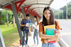 Gruppen-Lesebuch des Porträts der Studenten asiatisches zusammen lächelndes lizenzfreie stockbilder
