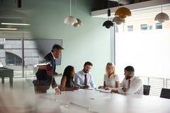 Gruppen-Sitzung um Tabelle am graduierten Einstellungs-Einschätzungs-Tag und Zusammenarbeiten auf Aufgabe, während, beobachtend d lizenzfreies stockbild