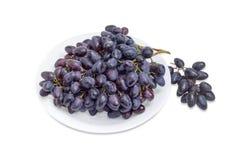Gruppen von blauen Trauben auf einem weißen Teller und dazu Stockfotos