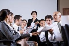 Gruppengeschäftsdarstellung, die Papiere austeilt Lizenzfreie Stockfotos