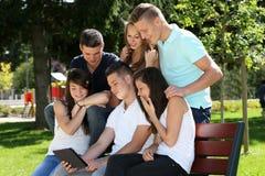 Gruppenjugendlicher und -tablette Stockfoto