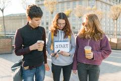 Gruppenjugendlichjunge und zwei Mädchen, mit einem Notizblock mit handgeschriebenem Wortanfang Stadthintergrund, goldene Stunde stockbilder