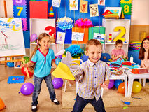 Gruppenkinder, die Origamiflugzeug im Kindergarten halten lizenzfreie stockbilder