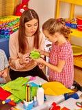 Gruppenkinder, die Origamiflugzeug im Kindergarten halten stockfotografie