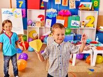 Gruppenkinder, die Origamiflugzeug im Kindergarten halten Stockfoto
