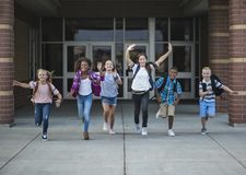 Gruppenschulschule scherzt Betrieb, während sie das Schulgebäude verlassen lizenzfreie stockfotos