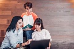 Grupper av asiatiska tonårs- studenter som använder att studera för bärbar datordator Arkivbilder