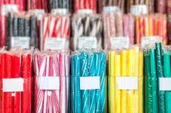 Grupper av godisen klibbar i olika färger som slås in i plast- cellofan Arkivfoto