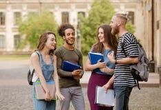Grupper, samtal och skratta för högskolestudenter gående Arkivfoton
