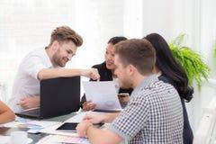 Gruppera affärsfolk som ser en bärbar dator under ett möte för presentation arkivfoto