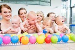 Gruppera bilden av mödrar och behandla som ett barn på begynnande simninggrupp royaltyfria bilder