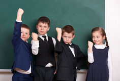 Gruppera eleven som en liga och att posera nära tom svart tavlabakgrund, grimacing och sinnesrörelse-, friendshp- och utbildnings Royaltyfri Bild