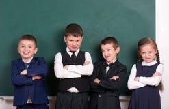 Gruppera eleven som en liga och att posera nära tom svart tavlabakgrund, grimacing och sinnesrörelse-, friendshp- och utbildnings Arkivfoton