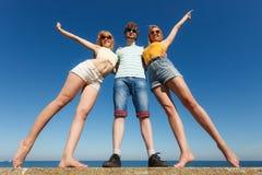 Gruppera flickor för vänpojke som två har utomhus- gyckel Arkivfoto