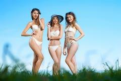 Gruppera fotoet av tre flickor i vita baddräkter, härliga flickor, Arkivfoton