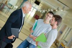 Gruppera högskolestudenter som talar till läraren på universitetkorridor royaltyfri foto
