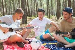 Gruppera lyckliga vänner med gitarren som har utomhus- gyckel royaltyfri fotografi