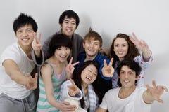 Gruppera ståenden av unga vänner som visar fredtecknet Royaltyfri Bild