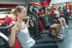 Gruppera unga vuxna människor som gör powerlifting på maskiner i idrottshall Royaltyfri Bild