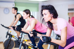 Gruppera utbildningsfolk som cyklar i idrottshallen som övar ben som gör den cardio genomköraren som cyklar cyklar Arkivfoto