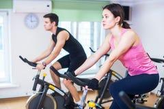 Gruppera utbildningsfolk som cyklar i idrottshallen som övar ben som gör den cardio genomköraren som cyklar cyklar Royaltyfri Fotografi