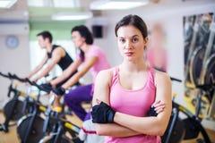 Gruppera utbildningsfolk som cyklar i idrottshallen som övar ben som gör den cardio genomköraren som cyklar cyklar Arkivfoton