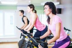 Gruppera utbildningsfolk som cyklar i idrottshallen som övar ben som gör den cardio genomköraren som cyklar cyklar Royaltyfri Foto