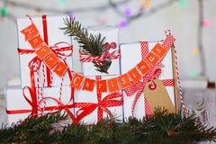Gruppera vita gåvaaskar för jul med röda band och glad jul för girland Royaltyfria Foton