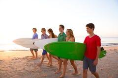 Grupperar tonåriga pojkeflickor för surfare att gå på stranden Royaltyfri Foto