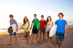 Grupperar tonåriga pojkeflickor för surfare att gå på stranden arkivfoto
