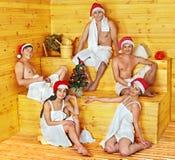 Gruppfolk i jultomtenhatt på bastu. Arkivfoton