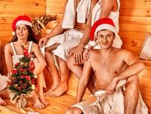 Gruppfolk i jultomtenhatt på bastu Arkivfoto